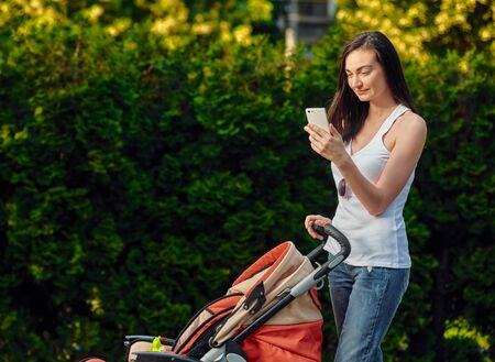 Happy mother with baby stroller using smartphone during walk Stockfoto