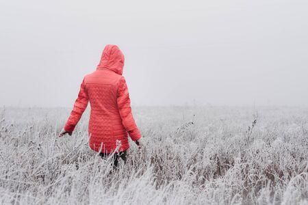 Woman in red coat walking in frosty field on foggy day Stockfoto