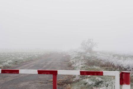 Barrier block abandoned road in foggy autumn field Stockfoto