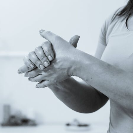 Closeup of professional strong female masseur stretching hands before procedure
