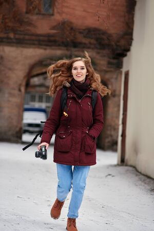 Happy female photographer with camera walking on winter street