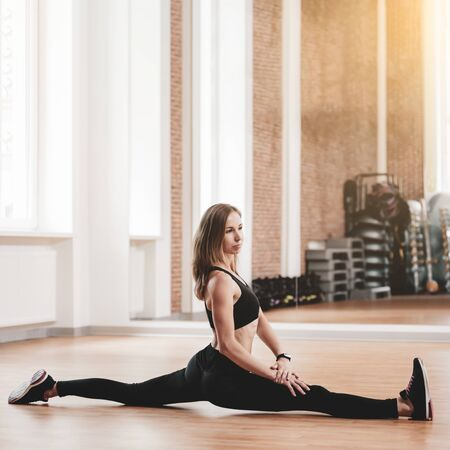 Portrait of healthy flexible woman doing split in modern gym