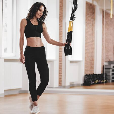 Sporty woman with fit body working-out with fitness straps in gym