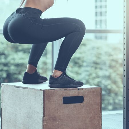 part of sporty woman doing box jumping in gym, image with cold vintage toning