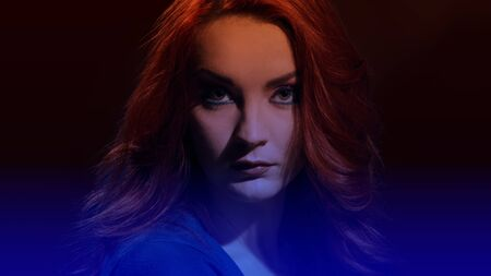 Portrait of attractive young woman with curly red hair and glamour makeup, image with soft dark blue gradient