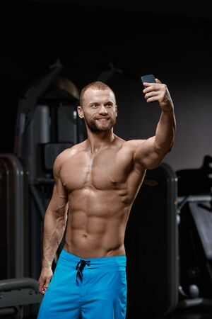 Handsome smiling man with muscular fit body making selfie in gym Stockfoto