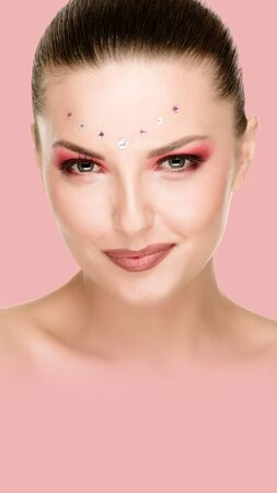 Beautiful woman with bright makeup and crystals on face, pink background. Aspect ratio and vertical position convenient for placement on a smartphone Stockfoto