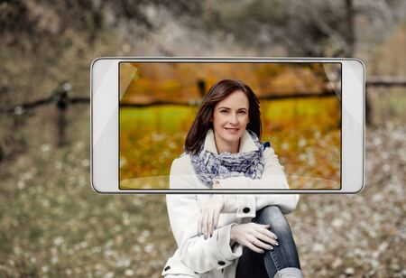 Portrait of beautiful happy woman sitting in forest, demonstration of device capabilities