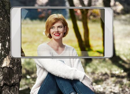 Smartphone displaying photo of beautiful smiling woman in autumn park