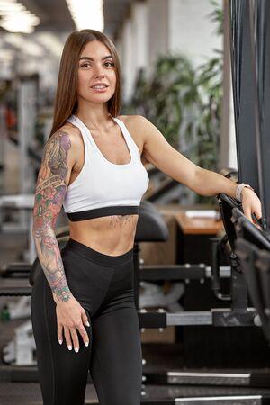 Portrait of young beautiful athletic sportswoman posing in modern health club
