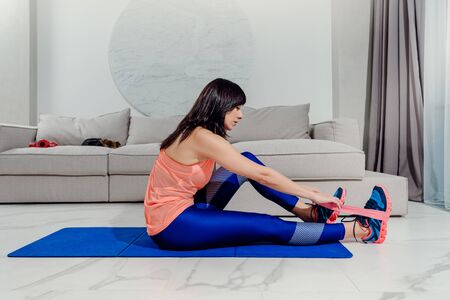 Young athletic woman sitting on mat and doing resistance training