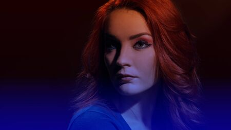 Portrait of beautiful redheaded woman with curly hairstyle and bright makeup, image with soft dark blue gradient