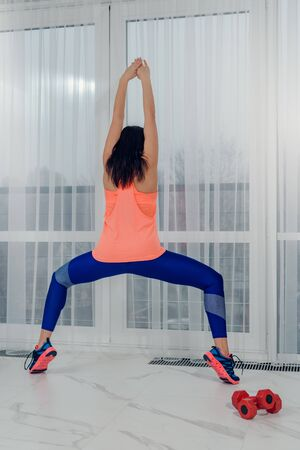 Back view of slim athletic woman doing yoga asana infront of window