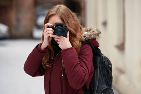 Young attractive woman photographer taking photos in winter city