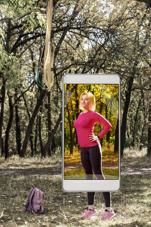 Young sporty woman having training in park, concept of new features in smartphone s camera Stockfoto