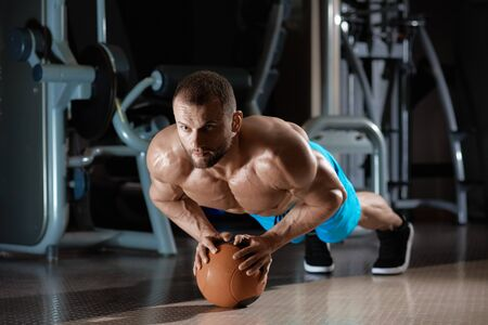 Portrait of muscular bodybuilder training in gym and doing push-ups on crossfit ball Stockfoto