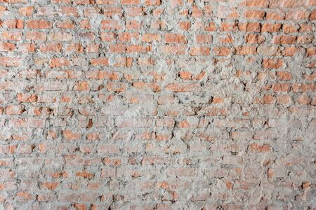 Closeup of old cracked red stone wall background Stockfoto