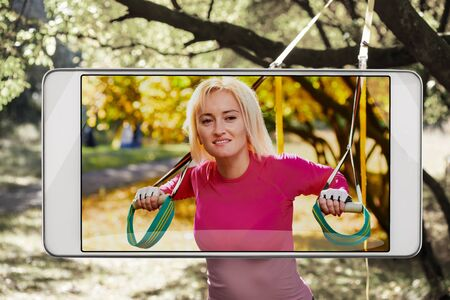 Smiling sportswoman doing resistance training in park, saturated image in smartphone s camera