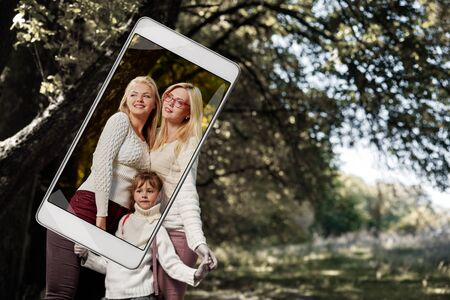 Portait of happy smiling girls posing with little sister in autumn park, smart device concept