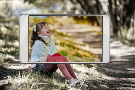 Photo of little laughing girl sitting in autumn park, demonstration of device capabilities