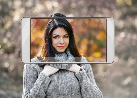 Smartphone displaying photo of beautiful young woman walking in autumn park