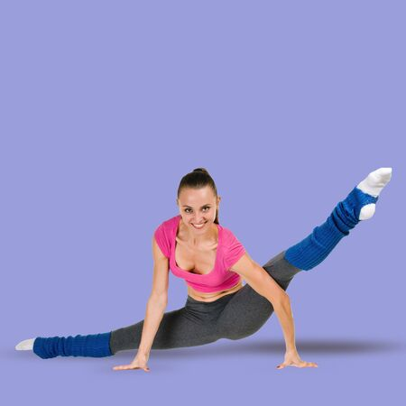 Beautiful young flexible woman stretching legs on royal shade violet background 写真素材