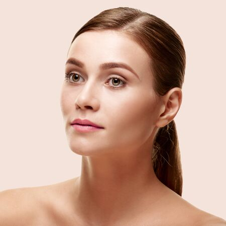 Portrait of young beautiful natural woman with perfect skin on light pink background