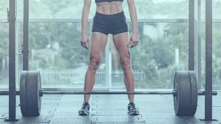 Part of strong fit young woman preparing for lifting barbell, image with cold vintage toning