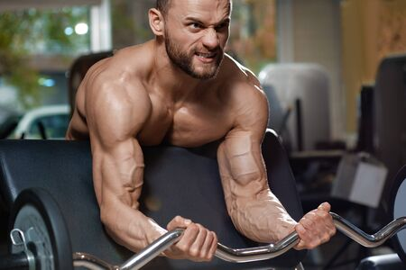Portrait of young healthy strong athlete doing powerlifting exercise in gym