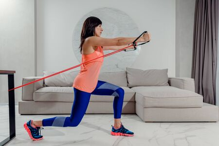 Young sportswoman doing exercises with rubber band at home
