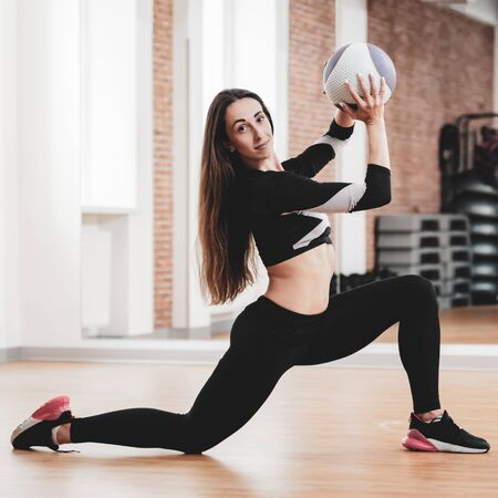 Fit young sportswoman stretching with ball in modern fitness club Stockfoto
