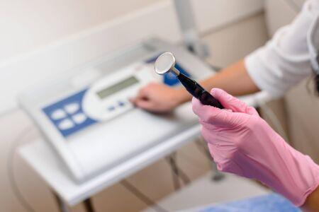 Closeup of professional cosmetologist holding ultrasound peeling equipment Stockfoto