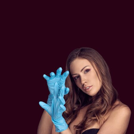 Beautiful female model wearing blue latex gloves on dark red color background
