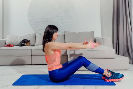 Young healthy woman doing fitness exercises at home