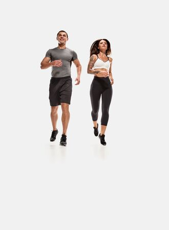 Strong man and woman running isolated on white background