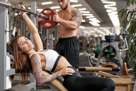 Personal fitness trainer helping young athletic woman with weightlifting Stockfoto
