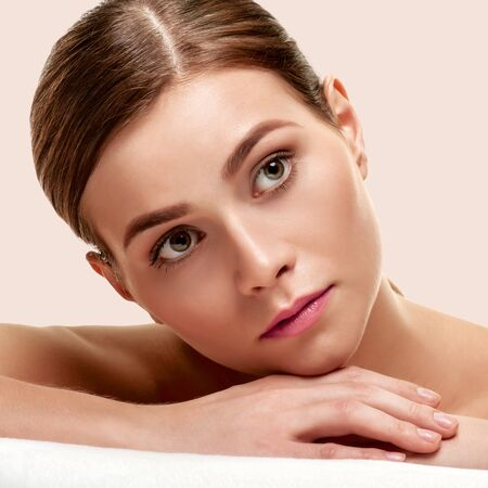 Portrait of young minded spa model with smooth soft facial skin on light pink background