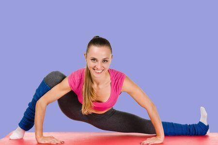 Happy athletic woman doing gymnastics on sport mat Stockfoto