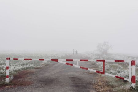 Red and white road barrier on foggy autumn day and poorly distinguishable silhouettes of two people