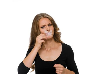 Young blonde trying to take off adhesive tape from her mouth after end of diet Stock fotó