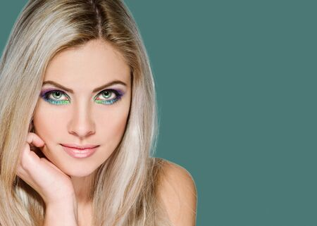 Portrait of young beautiful blonde with bright makeup on pine shade green background