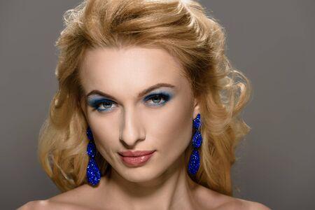 Hermosa mujer elegante con accesorios de lujo azul mirando a cámara Foto de archivo