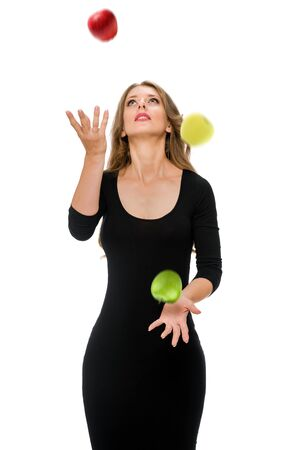 Beautiful fit young woman in black dress joggling with apples Banque d'images