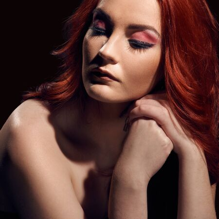 Fashionable portrait of beautiful redheaded model with naked shoulders on black background