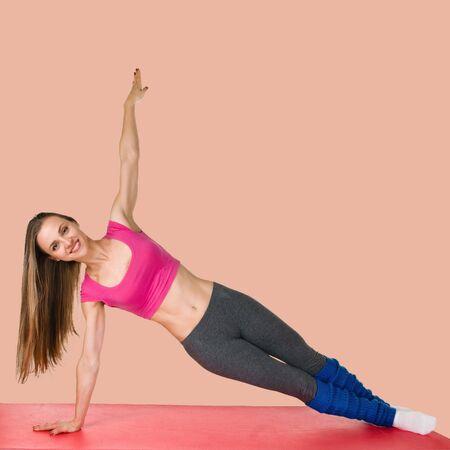 Attractive young slim muscular woman doing side plank