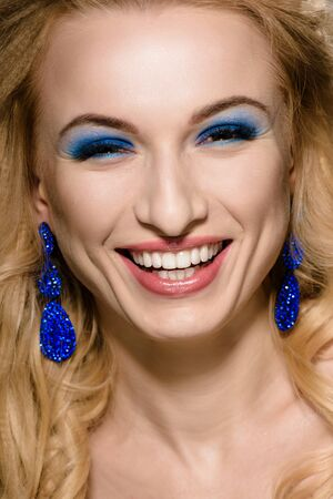 Beautiful young laughing woman with vogue make-up and stylish jewelry