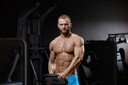 Strong athletic sportsman doing exercises with weightlifting plate in gym