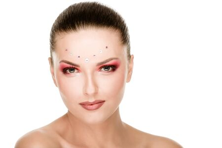 Portrait of beautiful young woman with artistic rhinestones makeup
