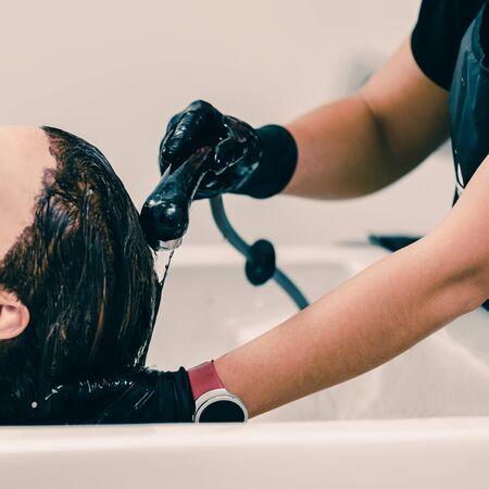 Beautiful brunette woman during hair wash in beauty salon