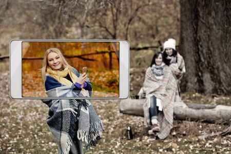 Young woman making photo in park, concept of new features in smartphone s camera